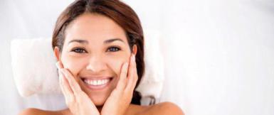 Frau fühlt die eigene Haut nach der Gesichtsbehandlung.