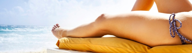 Frau im Bikini auf einer Liege am Strand. Fokus auf Beine und Meer.